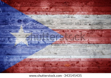 A vignetted background image of the flag of Puerto Rico onto wooden boards of a wall or floor. - stock photo