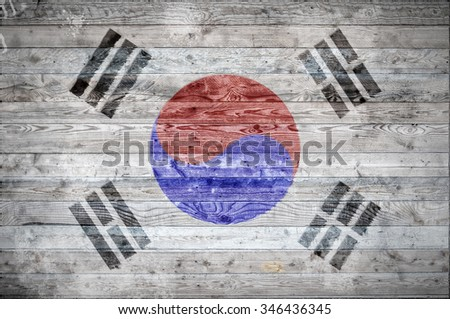 A vignetted background image of the flag of South Korea onto wooden boards of a wall or floor. - stock photo