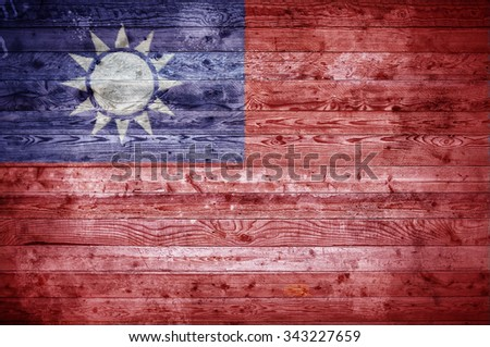 A vignetted background image of the flag of Taiwan onto wooden boards of a wall or floor. - stock photo