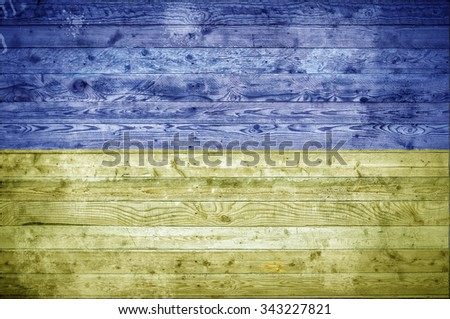 A vignetted background image of the flag of Ukraine onto wooden boards of a wall or floor. - stock photo