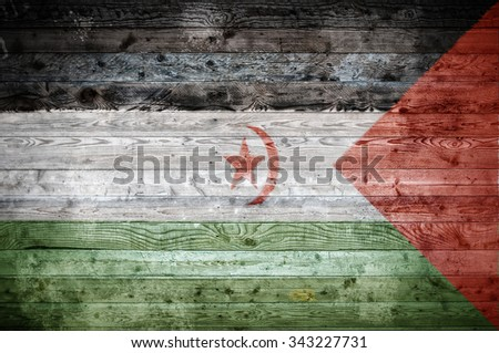 A vignetted background image of the flag of Western Sahara onto wooden boards of a wall or floor. - stock photo