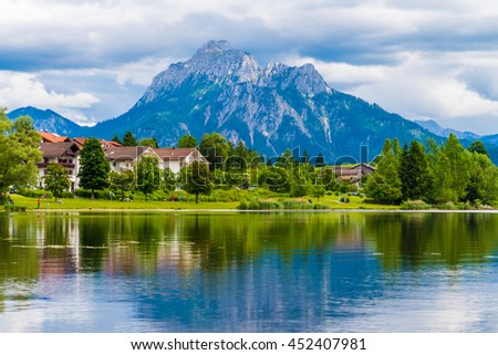 a village near the lake and the mountains on the horizon - stock photo