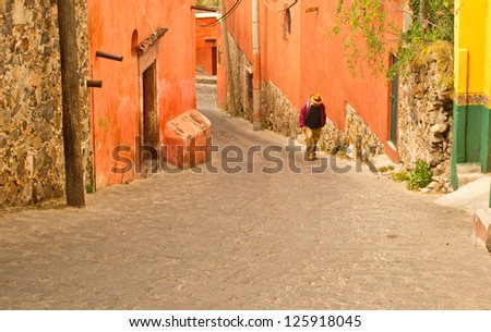 A villager trudges up a hilly street in San Miguel de Allende in colonial Mexico - stock photo