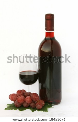 a vine bottle and a glass with grapes