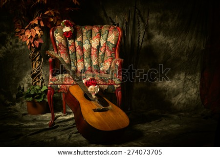 A vintage acoustic guitar leans against an empty, antique patterned armchair. Shot in chiaroscuro style lighting with room for your copy. - stock photo