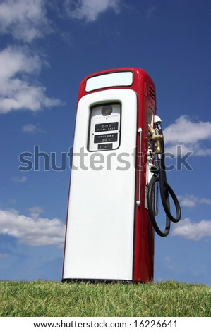 A vintage antique Gasoline fuel pump sitting on a grassy hill against the blue sky.