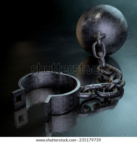 A vintage ball and chain with an open shackle on a dark backlit studio background - stock photo
