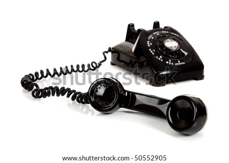 A vintage black telephone  with a white background - stock photo