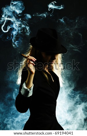 A vintage blond woman smoking a cigar isolated on dark background - stock photo
