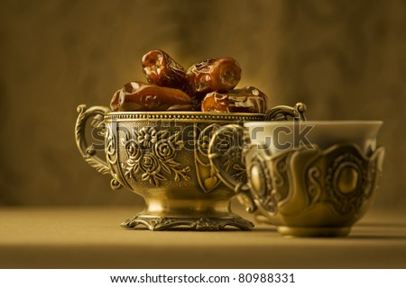 A vintage bowl of dates and a cup of tea. - stock photo