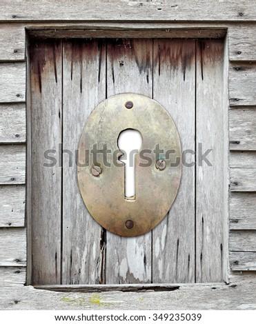 A vintage brass metal keyhole plate in an old timber window frame.  - stock photo