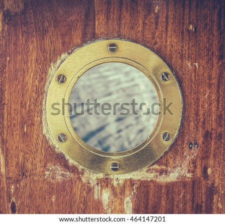 A Vintage Brass Or Bronze Porthole In A Ship's Door With Ocean Water Visible