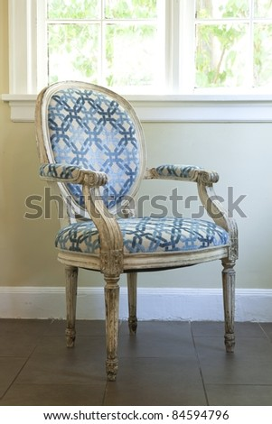 A vintage chair near a window - stock photo
