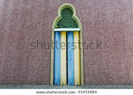 A vintage colorful decorative metal folding door with moorish motif on a grungy mosaic wall. - stock photo