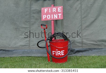 A Vintage Fire Point with a Bucket Hose and Pump.