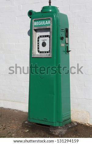 A vintage Gas/Petrol pump near an old garage. - stock photo