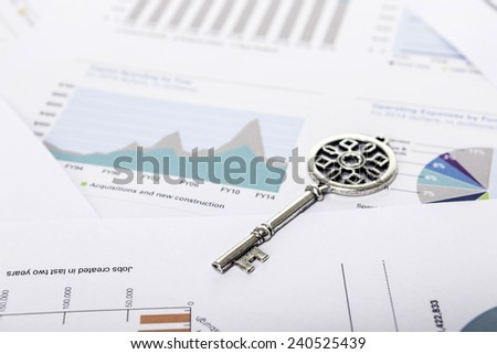 A vintage key on the graph paper(document)s for business. - stock photo