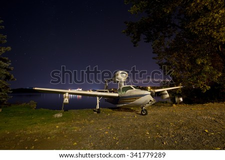 A vintage LAKE plane parked on the sandy shore of a lake. - stock photo