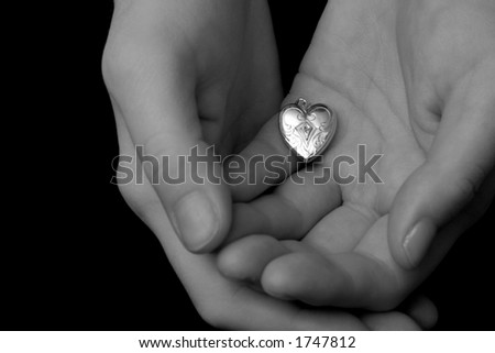 A vintage locket of a heart is held cradled in the palms of a woman's hands, as if she is tentatively offering her heart to someone.  Image is in black and white. - stock photo
