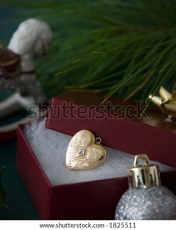 A vintage locket shaped as a heart lies open in a box with a small Christmas bow on top.   A branch of a Christmas tree and ornaments help show this is a Christmas present. - stock photo