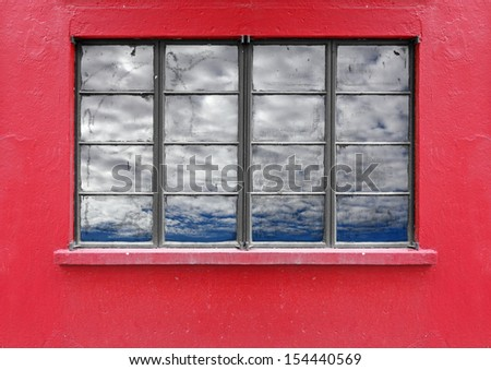 A vintage metal frame folding window on a red mason wall, with reflection of a blue cloudy sky on its glass pane. - stock photo