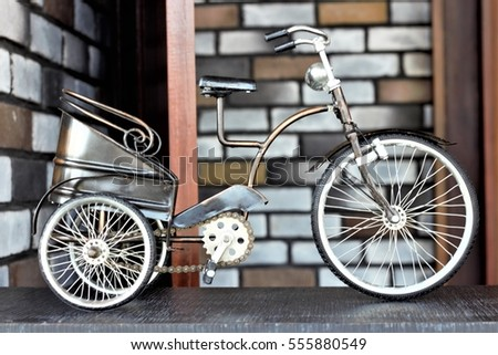 A vintage miniature tricycle carriage is on the front desk as a valuable antique decorative item for home or office decoration
