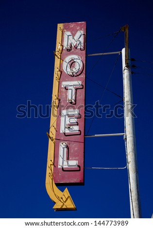 A vintage motel sign with an arrow in frount of blue sku - stock photo