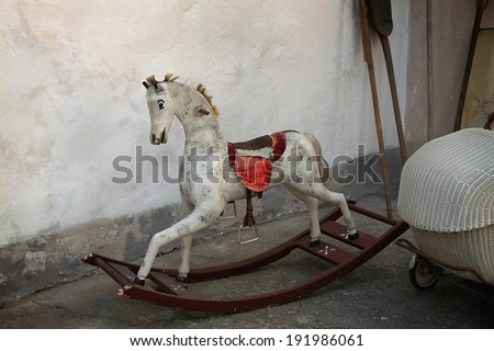 A vintage old rocking horse in a rustic setting. - stock photo