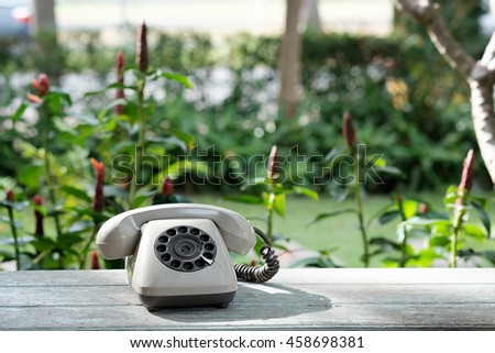 A vintage or old Retro rotary telephone on wood table with outdoor park. - stock photo