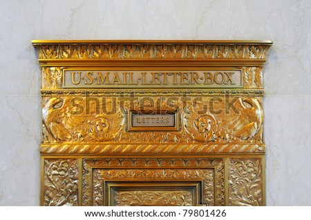 A vintage, ornate, gilded mail drop box in a city building - stock photo