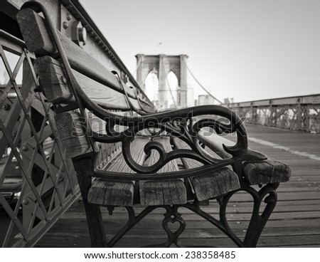 A vintage park bench on the Brooklyn Bridge facing Manhattan in black and white. - stock photo