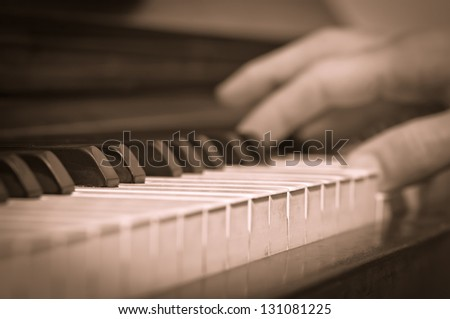 a vintage photo of a man playing on a piano