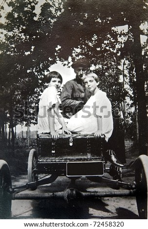A vintage photo of two girls and a man in an automobile.  It is on textured paper and shows signs of wear. - stock photo