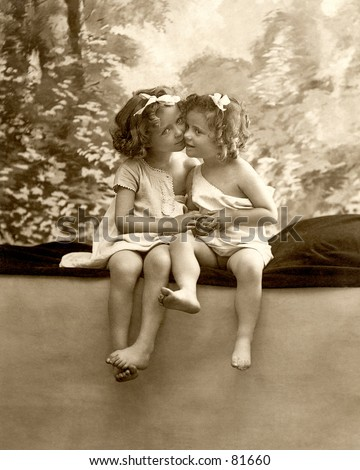 A vintage photograph (c. 1900) of two little girls cheek-to-cheek, hugging, and holding hands - used originally as a Valentines greeting.