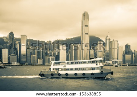 A vintage shot of a ferry sailing past the Hong Kong skyline. - stock photo