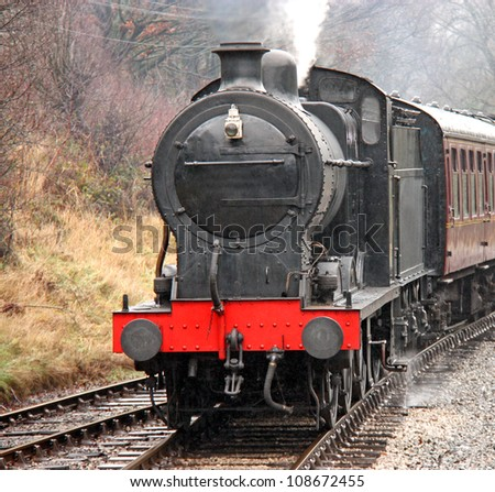 A Vintage Steam Engine Pulling Traditional Carriages. - stock photo