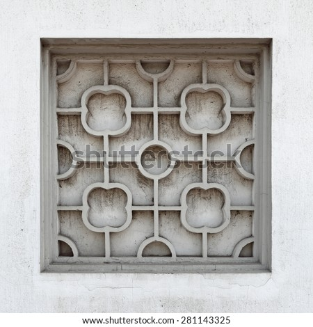 A vintage stone mason window frame with exotic clover symbol pattern. - stock photo
