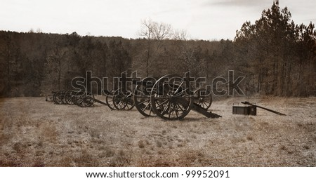 A vintage textured antique representation of an old photo of a battery of civil war cannon lined up for battle. - stock photo