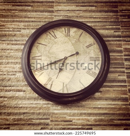 A vintage wall clock's hands approach seven o'clock. - stock photo