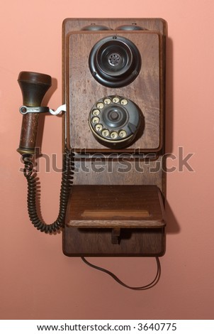 A vintage wooded telephone hung of a wall - stock photo