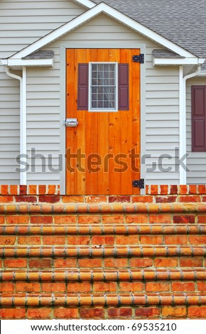 A vinyl window with shutters in a shellacked door on a vinyl sided house with a brick staircase leading up to it in a ranch house - stock photo