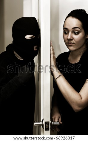 A Violent Intruder Bashes On A Door While A Female Occupant Hesitantly Opens Up - stock photo