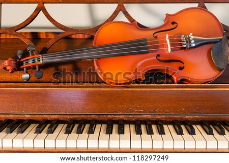 A violin rests on an old upright piano.
