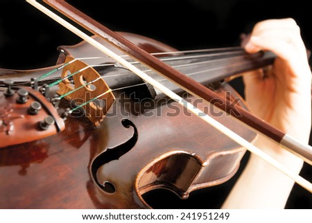 A violinist holding a violin or fiddle on a black background - stock photo