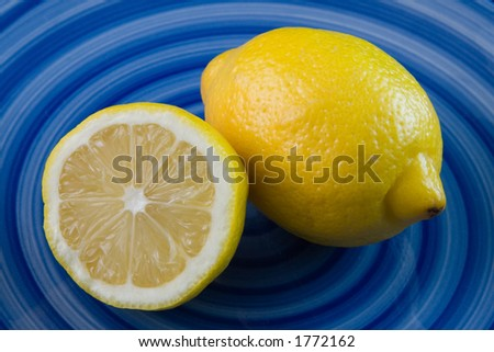A vivid picture of  a sliced bright yellow lemon resting against a whole lemon.  Both lemons are sitting on a deep blue plate with a swirled pattern of different hues of blue. - stock photo