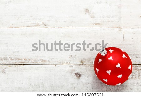 A vivid red bauble dotted with white hearts suitable as a Christmas or Valentines decoration on a background of white wooden boards with copyspace - stock photo