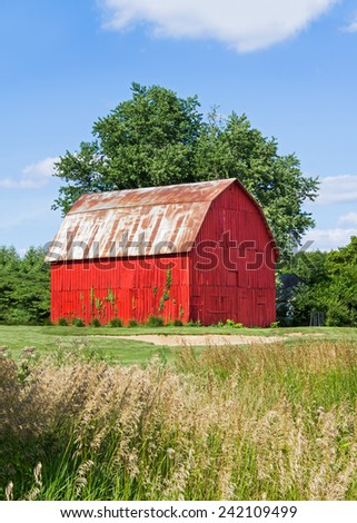 A vivid red wooden barn is backed by a large tree and blue sky in Indiana. - stock photo