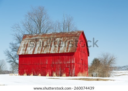 A vivid red wooden barn is topped with a rusty metal roof in a snowy landscape under a clear blue sky. - stock photo