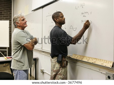 A vocational education teacher looking on as a student does equations on the board. - stock photo