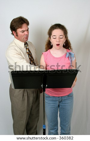 A voice coach teaching a student. - stock photo